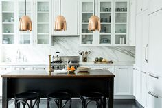 Marble walls and copper pendants in a kitchen designed by Katie Martinez. | Lonny September 2014