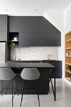 Kitchen Ideas - Matte black cabinets have been paired with dark countertops, creating a modern kitchen that contrasts the white walls. #BlackKitchen #KitchenIdeas #MatteBlackCabinets