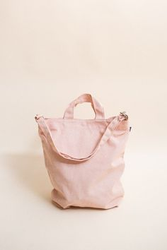 A perfect everyday tote in durable recycled cotton canvas duck in a pretty pastel shell pink color. Two handles and 40 in. adjustable strap, to carry in hand or over shoulder. - 16 in. H x 10 in. W x
