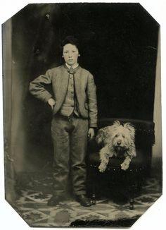 Boy and adorable, fuzzy dog on ottoman.