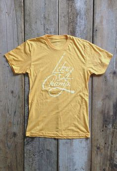 Like a Champ (Gold) Trusted Quality 50/50 blend American Apparel tee in Heather Gold. Subtly distressed front and inside tag printed with white soft-hand ink for a comfortable, vintage wear. Made in USA. Designed in Philadelphia.
