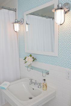 Chic bathroom with Quadrille Fabrics China Seas Edo  Grey on White Wallpaper, polished nickel marine sconces, white mirror, vintage glass shelf, subway tiles backsplash and glossy white pedestal sink.