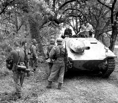 German infantry prepaid to move out with a Hetzer tank destroyer column. The Hetzer was based on the panzer 38(t) chassis.