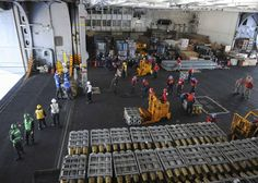 Sailors operate a connected replenishment station in the hangar bay of the aircraft carrier USS Theodore Roosevelt during an ammunition offload with Military Sealift Command dry cargo and ammunition ship USNS Amelia Earhart.   U.S. Navy photo by Mass Communication Specialist 3rd Class Chad M. Trudeau