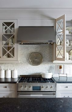 Sarah Richardson Design    Jenn Air stainless steel kitchen range & hood, marble mosaic fish tail tiles backsplash from Saltillo Tiles, light gray kitchen cabinets painted Para Paints Shoreline and honed black granite countertops.
