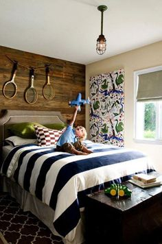 Great colors, bold stripe, geometric rug, fabric on canvas for wall, pretty wood panelling, nice upholstered headboard