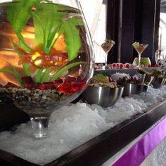 Небольшой аквариум с рыбкой дополнил собой стол с морскими яствами....