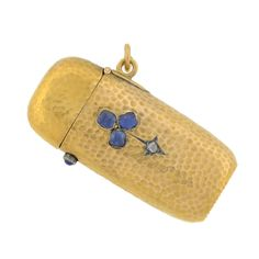 An interesting and unusual match safe from the Victorian period, circa 1880. This unique piece is made of 18kt yellow gold and has a rich, hammered surface set on the front with 3 sapphires and a single old rose cut diamond, set within a lovely trefoil design. Opens with a sapphire cabochon push clasp, the bottom is a ridged surface that acts a striker.