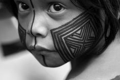 A beautiful portrait of a young Kayapó girl getting her body painted with geometric design in preparation for a ritual. Amazonia - Brazil - 2013 The photo avail