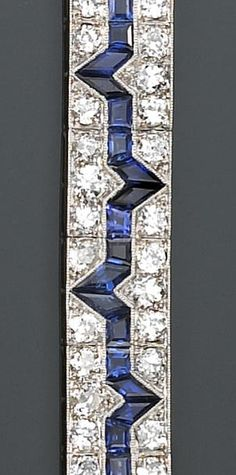 An art deco sapphire, synthetic sapphire and diamond bracelet  each rectangular-shaped panel set with alternately peaked lines of calibré-cut sapphires, within a millegrain surround of European and transitional-cut diamonds; estimated total diamond weight: 10.00 carats, mounted in platinum; length: 6¾in.