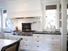 """The counters are from Walker Zanger (black honed granite and statuary marble).      How cute are those tiny cabinets below the hood corbels?"""