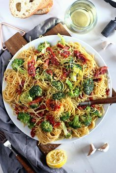 A large plate filled with angel hair pasta in a sun dried tomato, white wine, vegetable broth sauce. Also on the table is a glass of white wine and a wine cork, slices of Italian bread, a squeezed lemon, a fork with a wooden handle, cloves of garlic, and