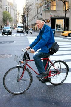 "BILL CUNNINGHAM  Occupation: Photographer for ""On the Street"" and ""Evening Hours"" columns in the New York Times Style section.    On his Schwinn bicycle wearing one of his French workman's jackets."