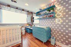 Parede cinza com poás brancas, móveis azul vintage e piso de madeira. O arco de madeira que passa por todo quarto também serviu de painel para televisão.
