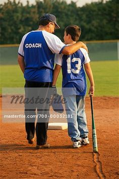 Back View of Baseball Coach and Young Player Walking in Field