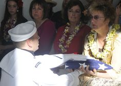 PEARL HARBOR (September 13, 2012) Master-at-Arms Second Class Drew Vitale presents Trish Anderson, daughter of Pearl Harbor survivor and former Master Chief Glenn Harvey Lane, with a flag during an interment ceremony held in his honor at the USS Arizona Memorial. Lane was served aboard the USS Arizona (BB-39) during the December 7, 1941 attacks on Pearl Harbor,and his ashes were buried with fellow shipmates lost during the attacks on Pearl Harbor. (U.S. Navy Photo by MC2 Tiarra Fulgham/Released)