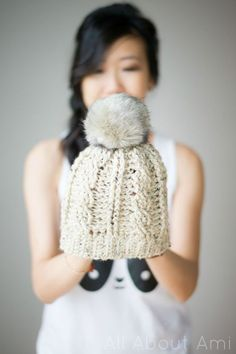Crochet this cute cabled beanie by All About Ami! Make it with just one skein of Vanna's Choice in Oatmeal (2 makes a slouchy version) and a 6 mm crochet hook. Top it with a faux fur pompom or make your own!
