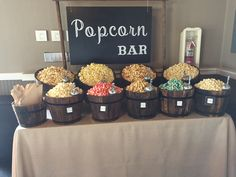 9 flavor Popcorn bar with wood planter barrels and a faux burlap tablecloth - candy bar - Flavored Popcorn, Popcorn Bar, Sweet 16 Themes, Sweet Buffet, Burlap Tablecloth, Fondue Party, Smoothies, Boho Wedding Decorations, Cute Wedding Ideas