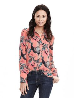 A tropical print top is styled with white skinny jeans.