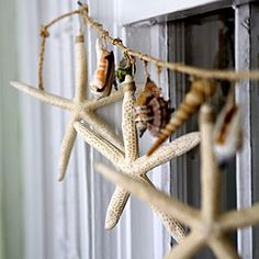 Using twine, create a garland of seashells, starfish, and any of your other coastal treasures. Attach the shells and starfish to the twine using additional pieces of thinner twine. If needed, use a small drill to make the holes in the shells. Hang your homemade garland to adorn a window. | SouthernLiving.com
