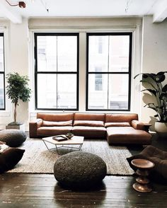 black steel-frame windows, camel leather sofa, jute rug