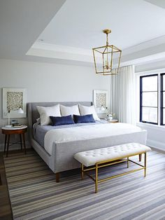 A Darlana Medium Lantern hangs from a tray ceiling over a gray tufted dining bench on a gold base placed on a gray and blue striped rug in front of a heather gray wingback bed dressed in white and blue bedding topped with white and blue pillows flanked by West Elm Penelope Nightstands topped with white swing arm table lamps positioned in front of framed art as a windows are concealed behind white curtains.
