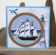 A Handmade Nautical Sailing Ship / Boat card suitable for a Birthday. Featuring a decorative partial Carrick Bend knot (not fully tightened to show the pattern between the 2 ribbon colours).  Set upon a 3-tone sea with seagulls in the sky behind and surrounded by a porthole cut from wood-patterned laminate.  Mounted upon a nautical lighthouse, shell and compass background and further mounted upon white cardstock edged with pearlescent blue ink. Measuring approx 15 x 15cm this is a striki...