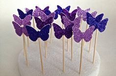 """24 Mixed Purple Glitter Butterfly Toppers  by TweedleDDesigns--these are basically 1""""x1"""" and glittered and colored on both sides which I like.  This is more my concept of 3D butterflies -- I know they're small but the colors are good and bunched together in a cascading """"river"""" they would look good.  I may buy 1 set if you lie them.  I will look at sugar ones again too, but I think the sticks are going to give you the 3D look you want."""
