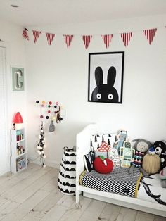 Love the black and white graphical prints mixed with pops of red in this toddler's bedroom