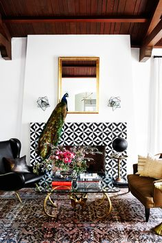 Bright living room with black and white tiles on the fireplace, exposed ceiling beams, gold mirror, and peacock