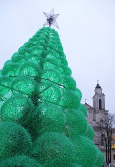 This 42 foot tall Christmas tree is located in Kaunas, Lithuania. Created by artist Jolanta Smidtiene, this eco-friendly tree is made of recycled green plastic bottles and zip ties. The tree is lit from the inside by lights. Recycled Christmas Tree, Tall Christmas Trees, Xmas Tree, Christmas Diy, Christmas Lights, Holiday Tree, Green Christmas, Christmas Decorations, Recycled Bottles