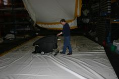 Just walk up and down your marquee. A roof 40ft x 20ft would take about 10 mins a side. You can see the clean marquees hanging up in the back ground. I used to do 4 roofs a day which took about an hour including folding the dry tents, scrubbing and handing up the next set to dry. In a week 20 roofs, over the winter (about 30 weeks my stock of 600 or so panels) Then the trick is to was the worst 4 roofs each day on a rolling program.