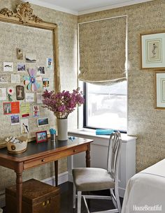 An antique framed bulletin board is covered in leftover wallpaper, with window-shade fabric to match.