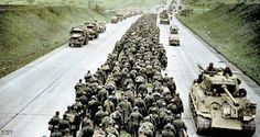 Thousands of German prisoners of war march along the central reservation of an autobahn as Allied vehicles drive past heading towards the front.Giesen, Germany. April 1945.