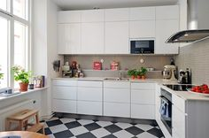 sleek white cabinets with black and white floors -- greige backsplash