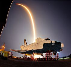 The SpaceX Falcon 9 launch, streaking over model of NASA's space shuttle at the Kennedy Space Center.