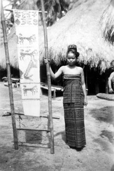 indigo textiles. Young woman from Kambera, Sumba, Indonesia wearing an ikat garment and with the warp for a cloth tied and ready for dying. 1931