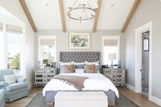 We love the exposed wood beams and vaulted ceilings in this custom home's bedroom! The pastel tones don't hurt either!