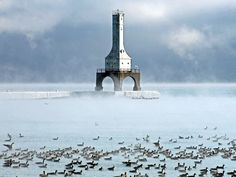 Wisconsin's Port Washington lighthouse appears through the mist as hundreds of birds huddle in Lake Michigan. Beacon Lighting, Beacon Of Light, Light In The Dark, Lighthouse Lighting, Lighthouse Photos, Lake Michigan Lighthouses, Costa, Port Washington, National Weather