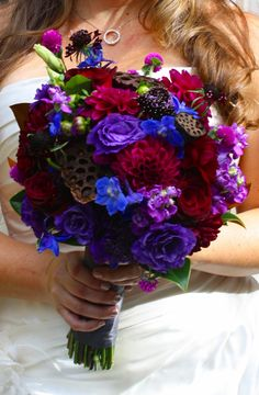 Jewel tone Brides bouquet. Burgundy, purple and blue flowers with added texture form lotus pods