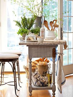 Place a salvaged slab of granite from a local supplier atop a sofa console to create a kitchen island with a slim profile. For a piece that can double as a breakfast bar, use a slab that overhangs on both sides. Add vintage hooks to hold dish towels or often-used utensils.