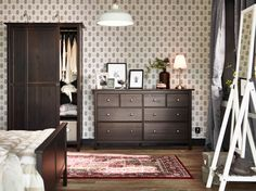 A large bedroom with a chest of drawers with 8 drawers and a wardrobe with sliding doors, all in black-brown.