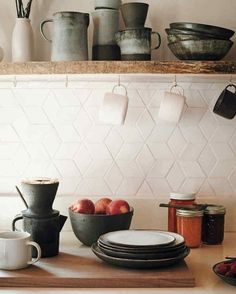 Cain's stoneware, shown here, consists of necessary tools for their daily routine, including coffee-brewing. The countertops are quartz composite from a local company. Cain learned how to fire the ceramic tiles herself to form the geometric backsplash. Kitchen Ikea, White Kitchen Backsplash, New Kitchen, Kitchen Dining, Kitchen Decor, Backsplash Ideas, Kitchen White, Hexagon Tile Backsplash, Copper Backsplash