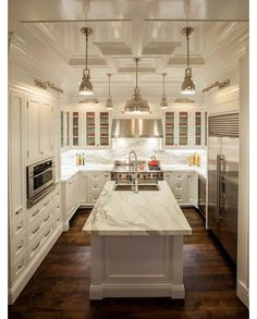 Kitchen design with white cabinets and pendant lighting.