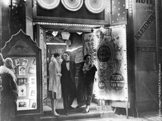 People mill around the doorway to a cabaret show in Germany.  Circa 1925