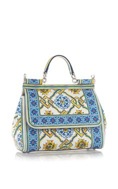 A celebration of Italy as seen through the eyes of tourists in post-World War II Italy was the theme for Stefano Gabbana and Domenico Dolce's Spring 2015 collection. This **Dolce & Gabbana** bag draws inspiration from Sicilian maiolica tiles for its intricate, colorful design.