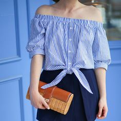 A striped off-the-shoulder top from Tuckernuck paired with a wicker clutch from J.McLaughlin