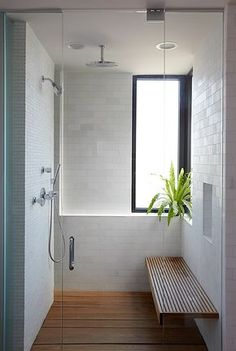 white shower with wood bench & floor