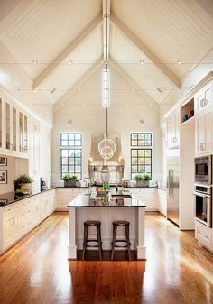 This kitchen! vaulted ceiling, wood floors, white cabinets, black countertops