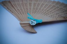 Sandalwood fans bought from a craft store decorated with thank you charms and ribbons in your wedding colors make fun and useful wedding favors guests can take home!